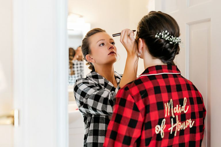 Festive Christmas Wedding Ideas Bride Putting Makeup on Maid of Honor